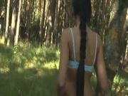 Brunette girl peeing in the forest