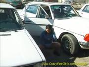 sweet girl peeing between the cars
