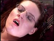 Horny redhead with glasses fingers her pussy and rubs her tits on the bed