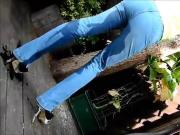 Young blonde standing peeing her jeans in garden and rubs