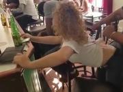 Une fille en jeans chauffe un mec dans un bar