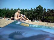 Young blonde girl sunbathing in public beach in Poland