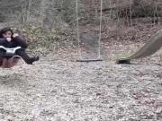 Kleine Teen pisst von der Schaukel auf einem Spielplatz