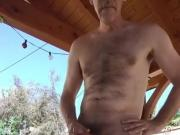 Standing fully naked and stroking cock outside