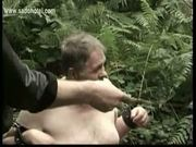 Slave tied to a tree is hit with a whip and master mastrubat