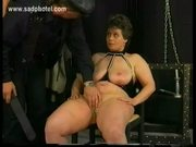 Older slave sitting in a chair is spanked on her bald pussy