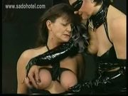Masked dominatrix in latex ties the big tits of slave with t