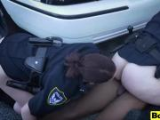 Two white police officers riding black suspect in public