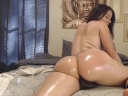 Seductive brunette shakes her juicy oiled butt on dildo