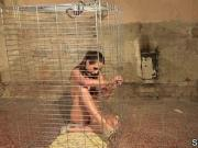Submissive babe orgasms in a cage while gagged