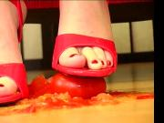 German woman crushing tomatoes with red high heels